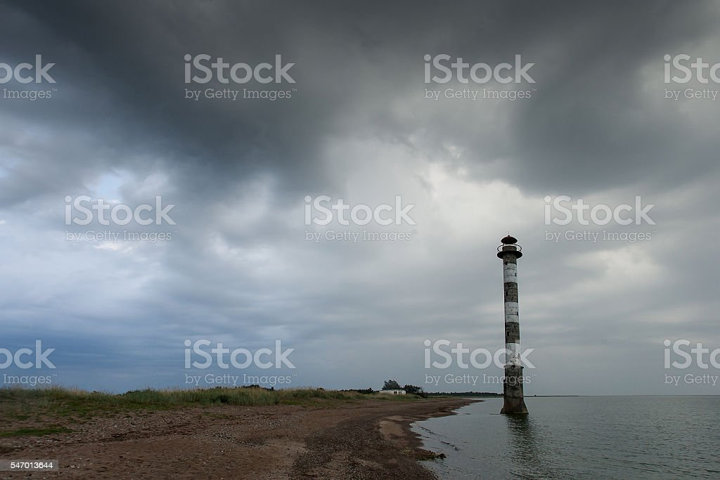 Skew lighthouse and Baltic Sea. Stormy night on the beach. stock photo
