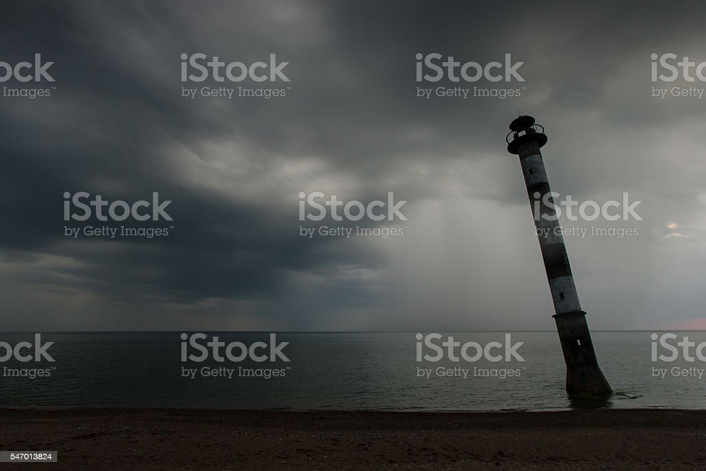 Skew lighthouse in the Baltic Sea. Stormy night on the beach. stock photo