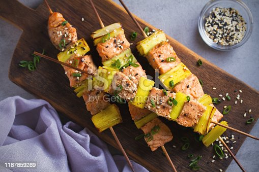 Skewered salmon teriyaki with leeks, sprinkled with sesame seeds on serving board. Overhead, horizontal