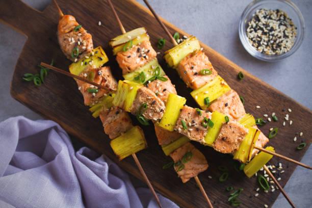 Teriyaki de salmón salpicado con puerros, espolvoreado salpicado de semillas de sésamo en tabla de servicio - foto de stock