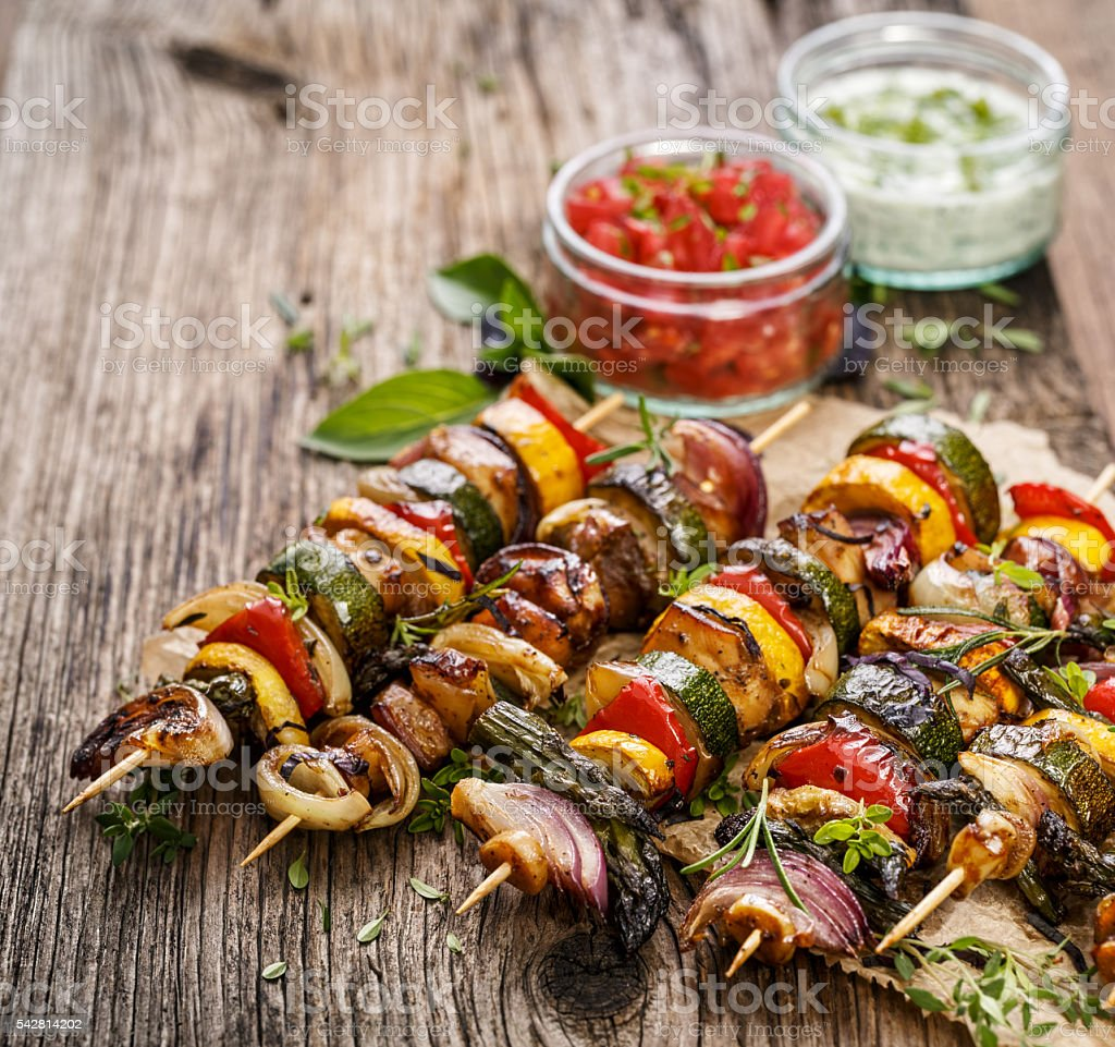 Skewers with vegetables and chicken meat on a rustic  table stock photo