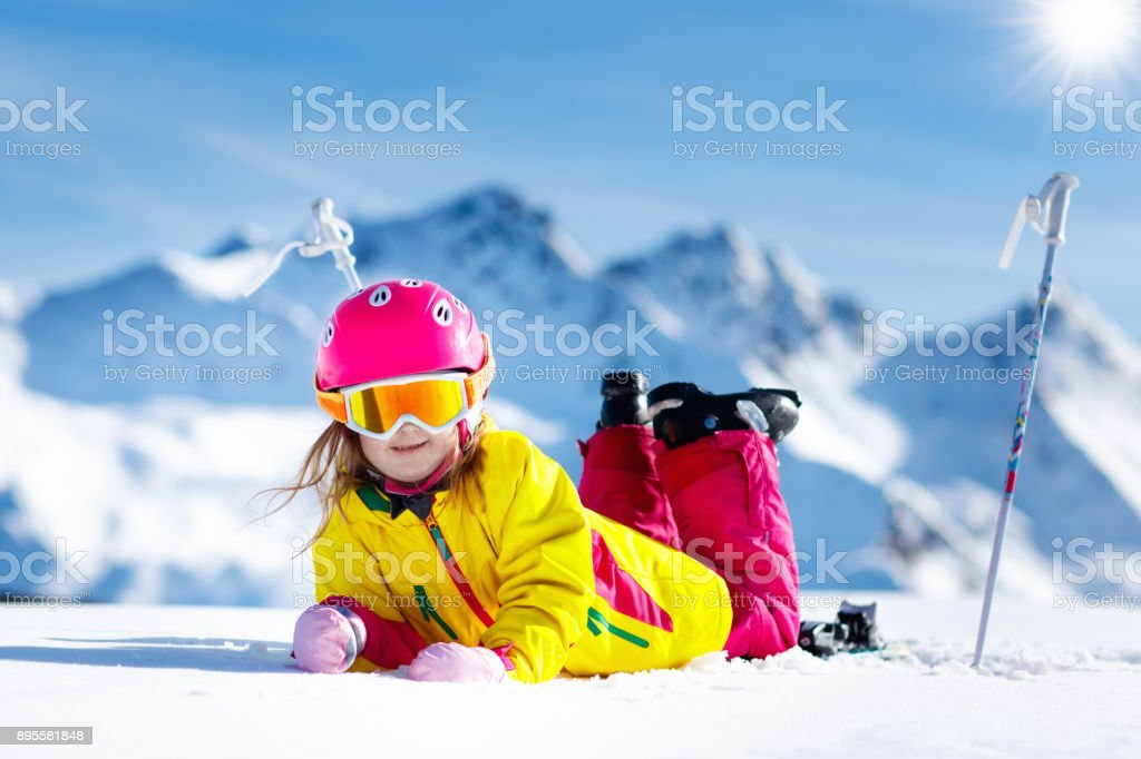 Child skiing in mountains. Active toddler kid with safety helmet,...