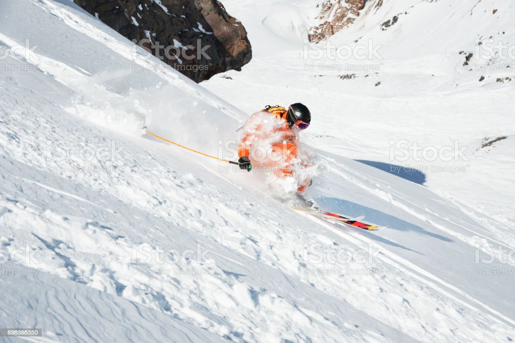 Ski athlete in a fresh snow powder rushes down the snow slope Ski athlete in a fresh snow powder rushes down the snow slope. The concept of winter ski sports Accidents and Disasters Stock Photo