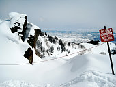 Cross section of mountain top with ski boundary sign, rocky crag and vanishing horizon