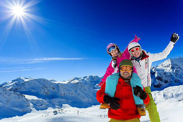 Ski family enjoying winter Ski, skier, sun and winter fun - family skiers  enjoying winter holidays ski holiday stock pictures, royalty-free photos & images