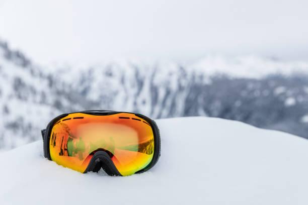 Ski Goggles at Mountain Ski Resort Ski Goggles at Mountain Ski Resort and mountains in the background ski goggles stock pictures, royalty-free photos & images