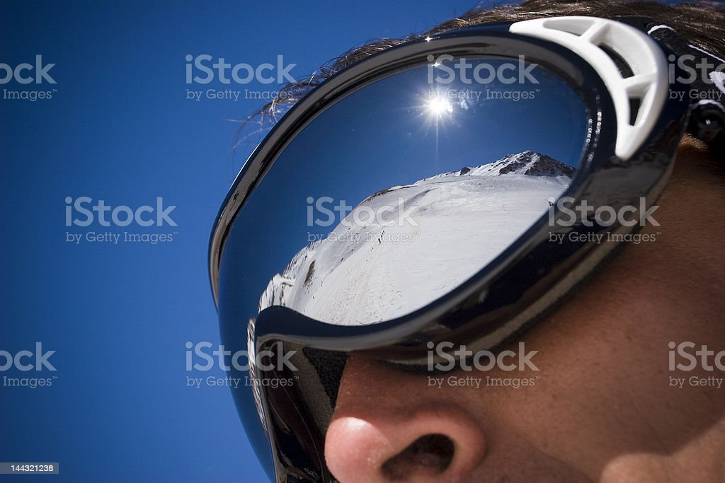 Ski goggles reflecting snow-covered mountain stock photo