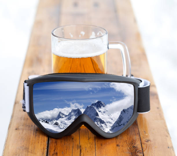 Ski goggles with reflection of mountains and glass mug with fresh cold beer - foto stock