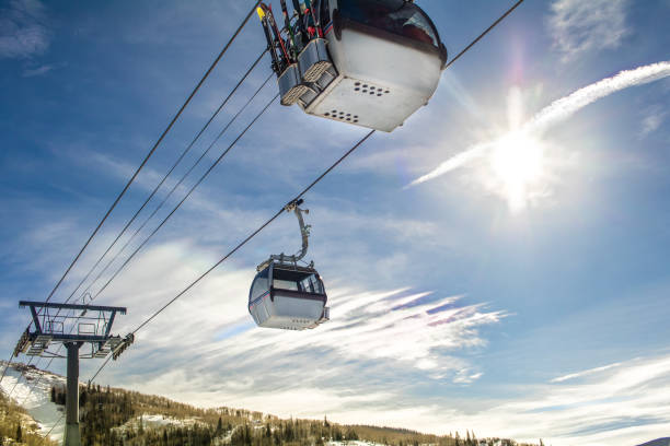 Ski gondolas in winter Ski gondola moving across the blue sky; sunlight lights the scene steamboat springs stock pictures, royalty-free photos & images