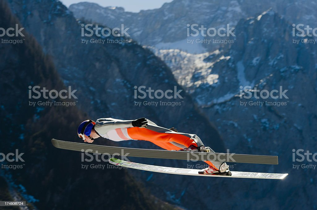 Ski jumper against the mountains stock photo