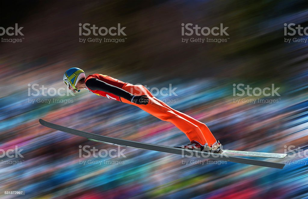 Ski jumper in mid-air against blurred background stock photo