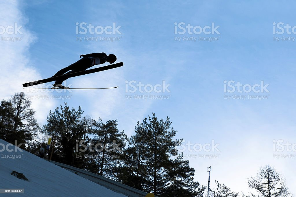 Ski jumper in mid-air against the blue sky stock photo