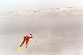 A male ski jumper takes flight on a foggy day.