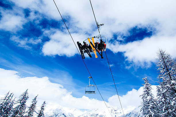 ski lift against blue sky French Alps, Haute Savoie - chair lift with three unrecognizable people against blue sky with clouds with mountains and snowy woods on the background vail colorado stock pictures, royalty-free photos & images