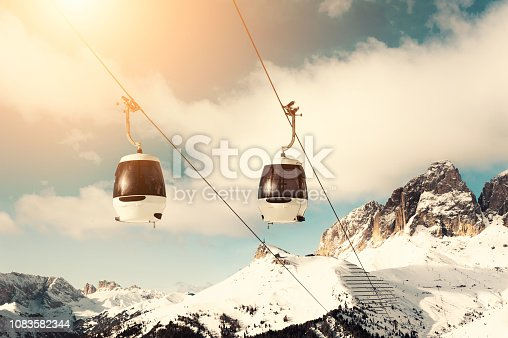 Ski lift cabin in ski resort in winter Dolomite Alps. Val Di Fassa, Italy. Vintage filter