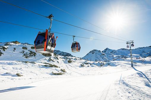 ski lift gondolas against blue sky over slope at ski resort on sunny winter day at Italy Alps