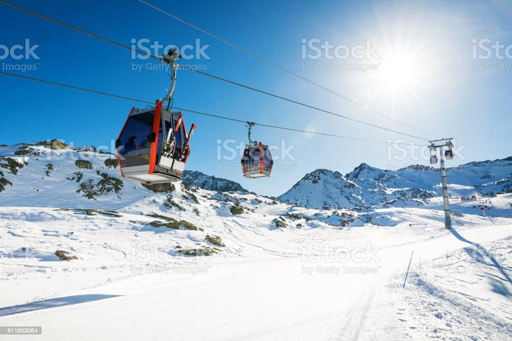 ski lift gondolas against blue sky over slope at ski resort on sunny winter day at Italy Alps stock photo