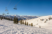 Ski Lifts in the snow covered back bowls of Vail Ski Resort under a clear blue sky in the Colorado Rocky Mountains