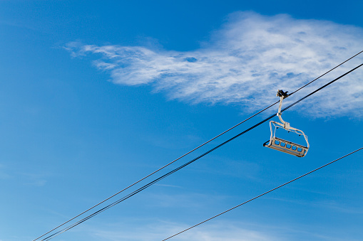 Ski lifts on background of blue sky with clouds