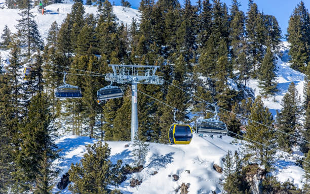 Ski lifts taking people to the top of a mountin in full sun stock photo