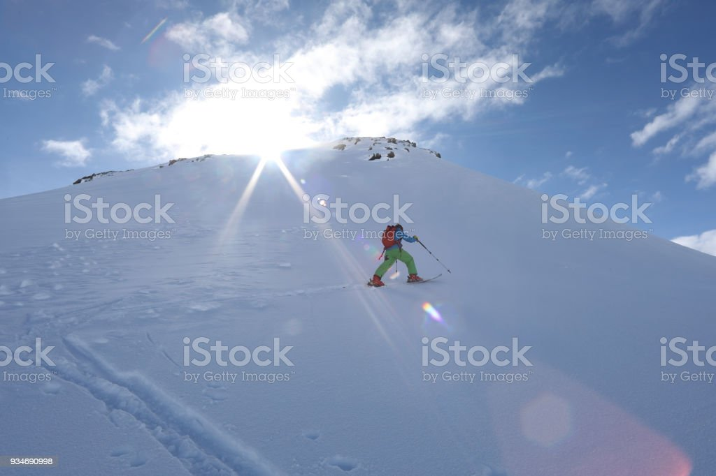 Ski mountaineer ascends slope towards mountain summit and sun. stock photo