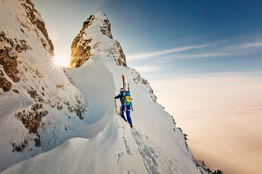 Ski mountaineer with crampons and ice ax- Freerider at the way to Summit - Alps