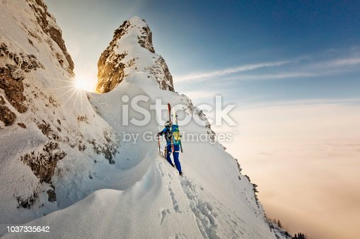 istock Ski mountaineer with crampons and ice ax- Freerider at the way to Summit - Alps 1037335642