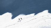 Ski mountaineers in the shadows of the mountains.