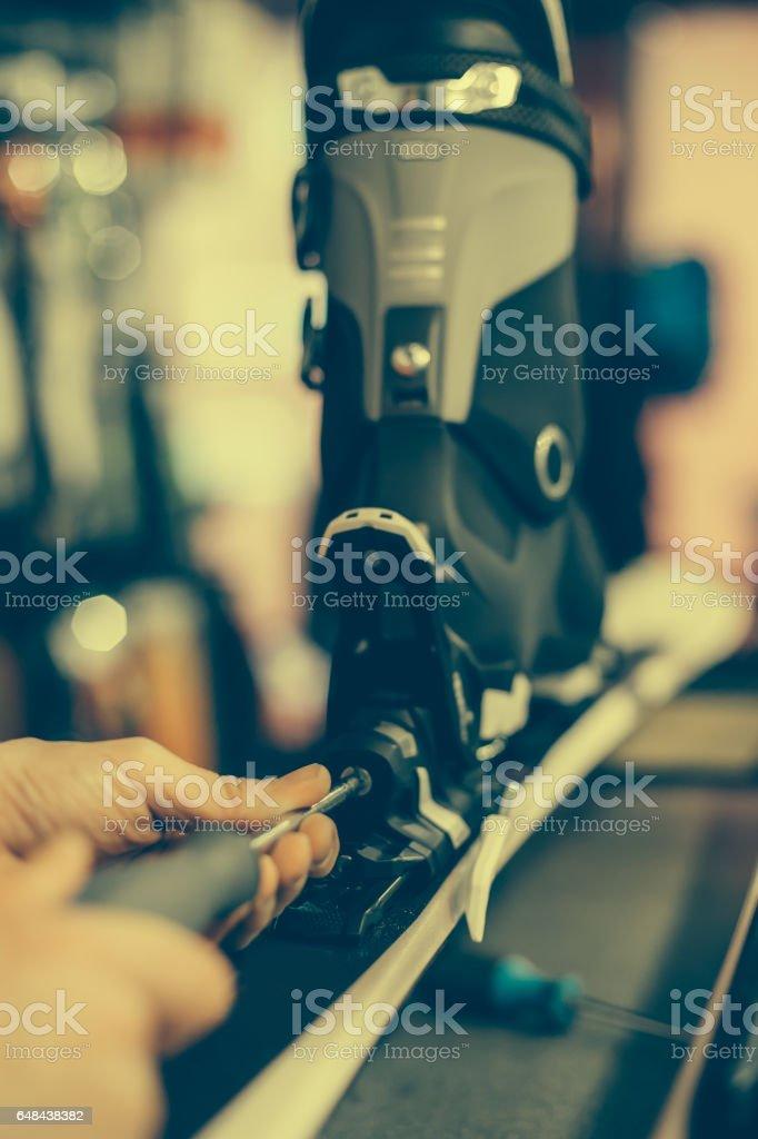 Ski repair shop worker adjust the bindings stock photo