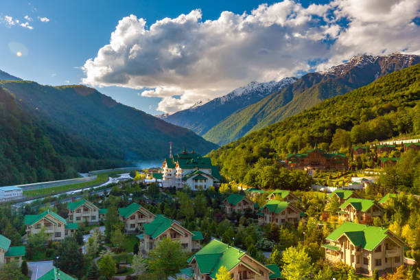 Ski Resort at Caucasus Mountains, Krasnaya Polyana, Sochi, Russia. Modern mountain cottages with green roofs against the backdrop of a mountain valley covered with a green spring sun forest. sochi stock pictures, royalty-free photos & images