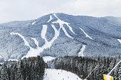 Skiers and snowboarders enjoying on slopes of ski resort Bukovel, Ukraine.