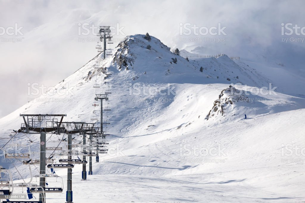 Ski resort closed due to Covid-19 Empty ski lift heading toward the top of the snow-capped mountain lost in the cloud. Andorra Stock Photo