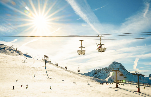 Ski resort glacier and chair lift in french alps - Winter vacation and sport travel concept - Snowboard season opening and people having fun on mountain - Warm afternoon color tone