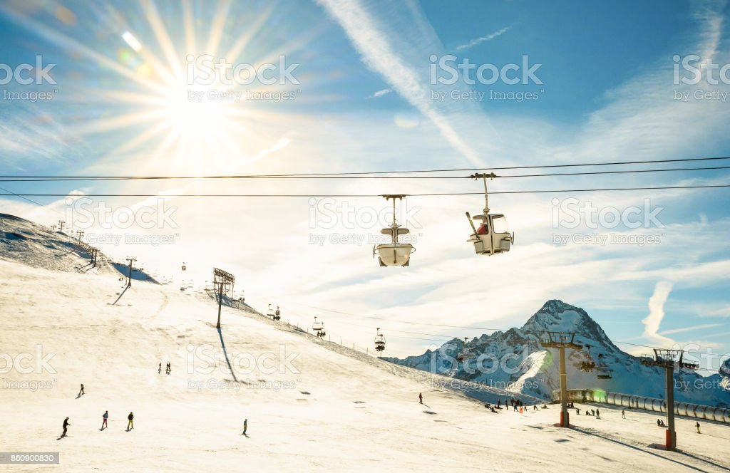 Ski resort glacier and chair lift in french alps - Winter vacation and sport travel concept - Snowboard season opening and people having fun on mountain - Warm afternoon color tone stock photo