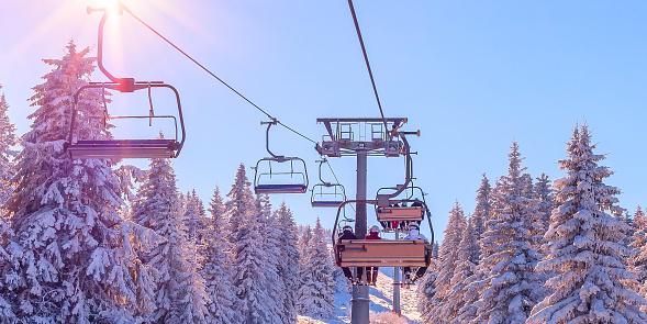Banner panorama of ski resort, skiers on the ski lift, white snow pine trees at pink sunset or dawn, Kopaonik, Serbia