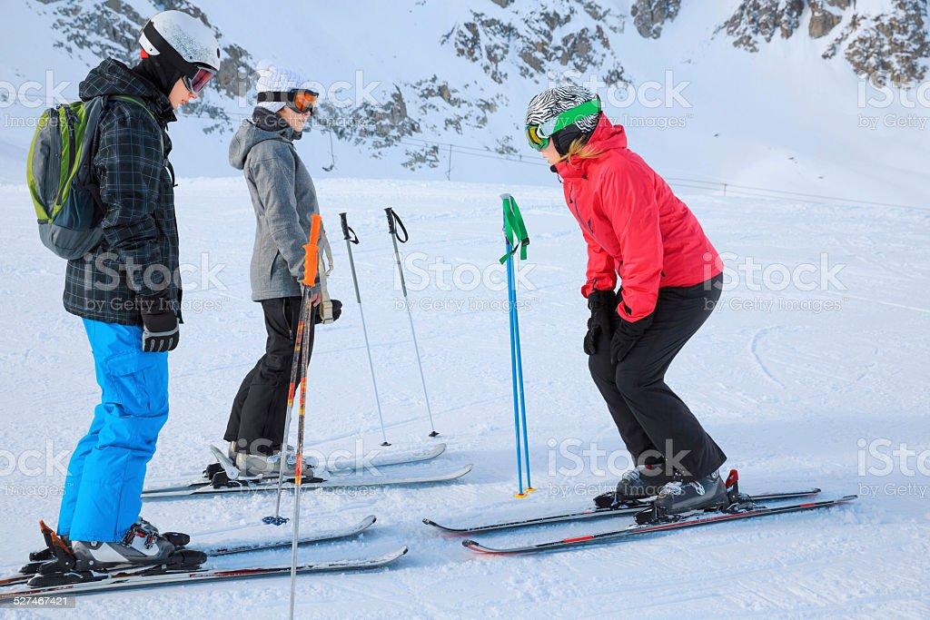 Ski School    Snow skier instructor teaching teenage girls and boys stock photo