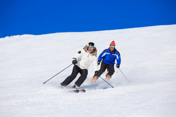 Ski school. Snow skiers skiing at sunny ski resort Dolomites mountain in Italy. Two friends skiing. Beautiful mountain landscape background. stock photo