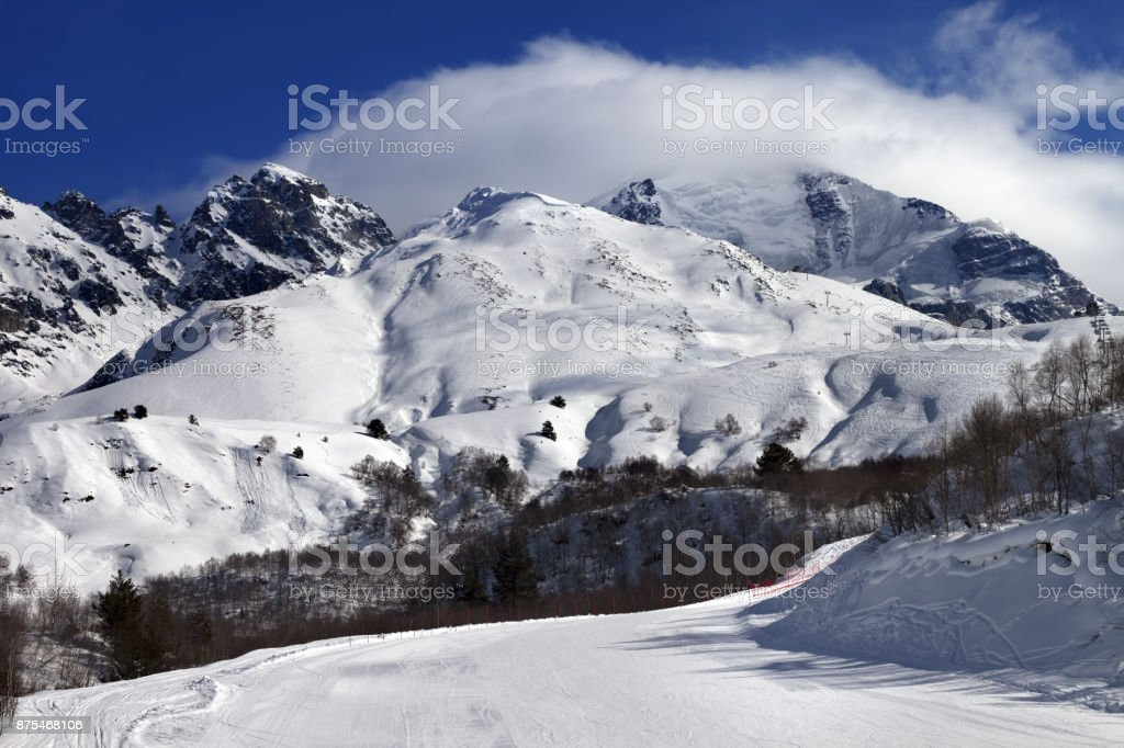 Ski slope and mountains in clouds at sunny day stock photo