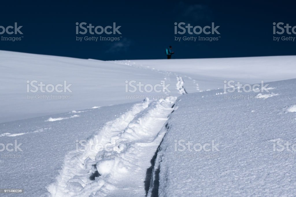 Ski touring track in powder snow with blurred skier background stock photo