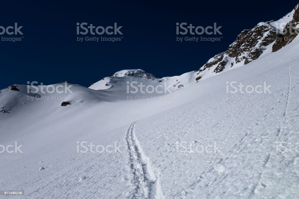 A ski touring track leading up to alpine mountain pass stock photo
