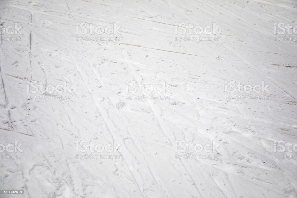 Ski traces on snow in mountains at sunny day stock photo