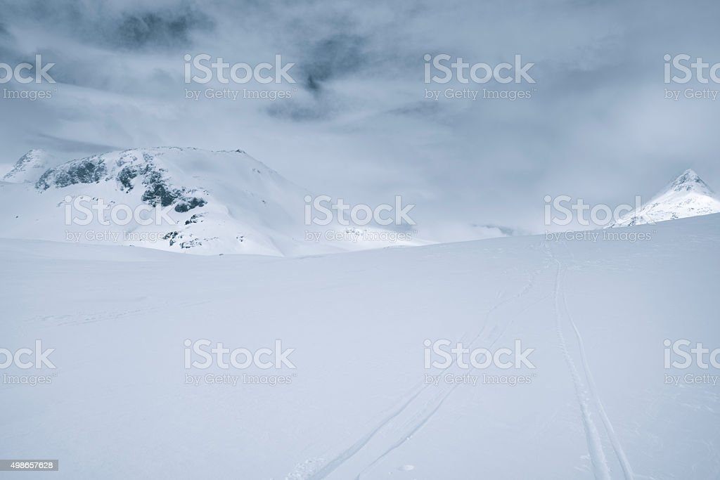 Ski tracks in the snow in winter mountains stock photo