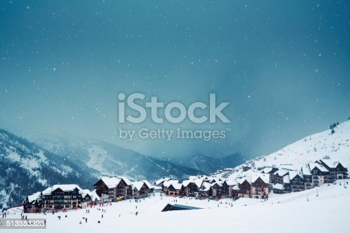 Mountain village and ski slope on a snowy winter day.