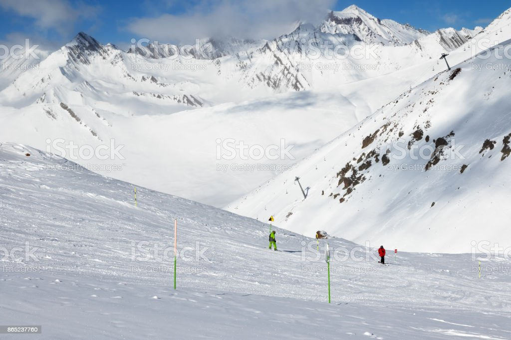Skier and snowboarder downhill on freeride trace and mountains in clouds stock photo