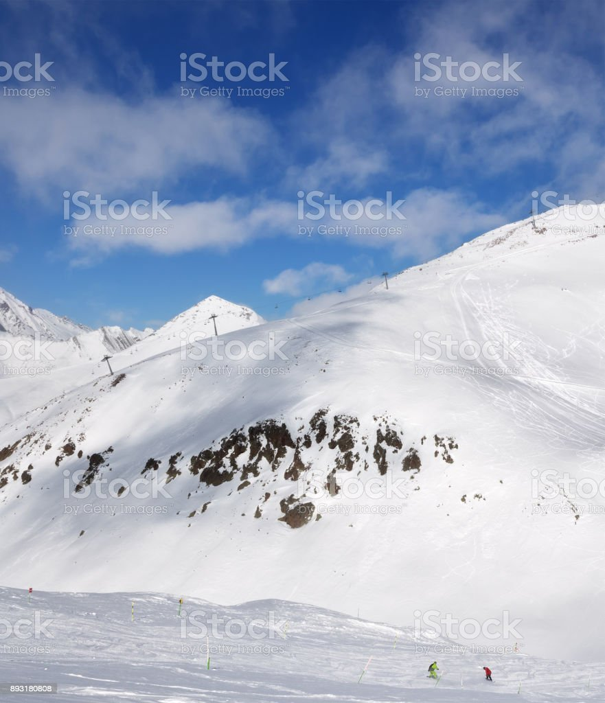 Skier and snowboarder downhill on trace and mountains with clouds stock photo