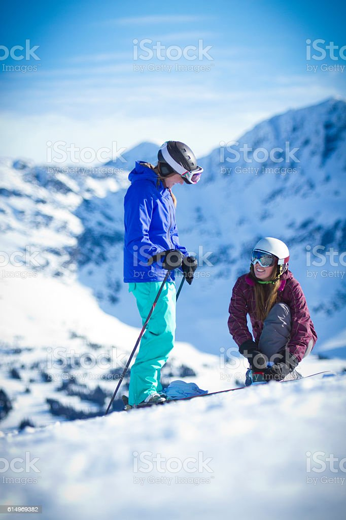 Skier and snowboarder getting ready for their run. stock photo