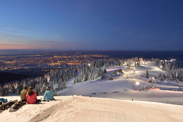 skier and snowboarder waiting for sunrise on Grouse stock photo