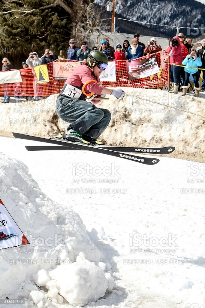 Skier being pulled over a jump while skijoring stock photo