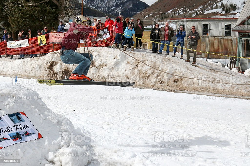 Skier clears a jump in a skijoring competition stock photo