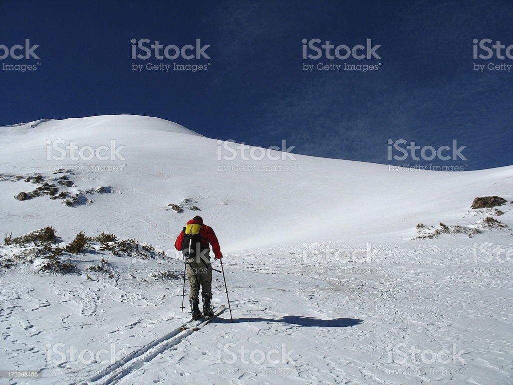 Skier climbing a peak. stock photo